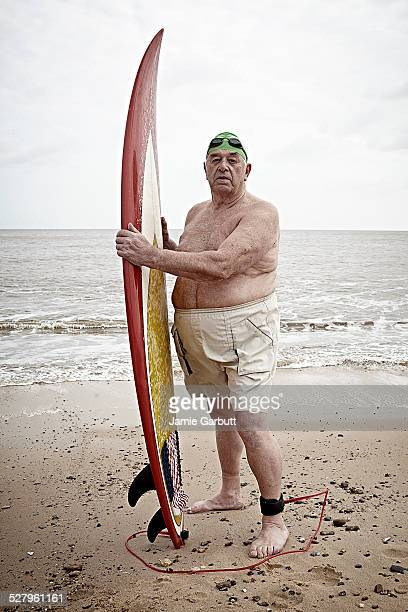 Elderly male surfer holding his surf board
