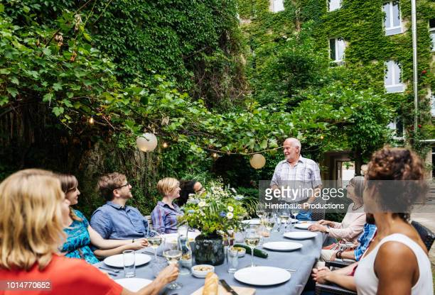 Elderly Man Addressing His Family During Outdoor Meal