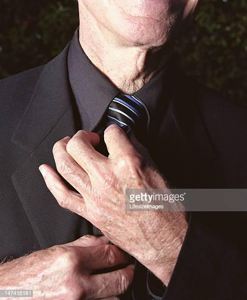 Regolazione cravatta uomo anziano, close-up