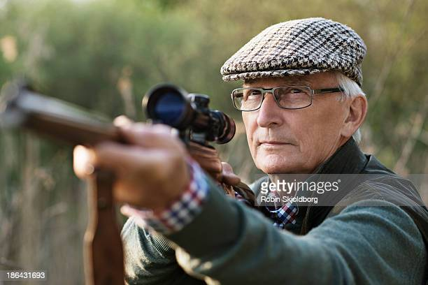 Elderly man aiming with rifle