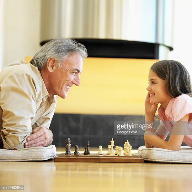 Elderly man and a young girl (12-13) lying on the floor playing chess