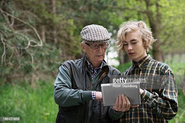 elderly man and boy in forrest looking at tablet computer - generation gap stock pictures, royalty-free photos & images