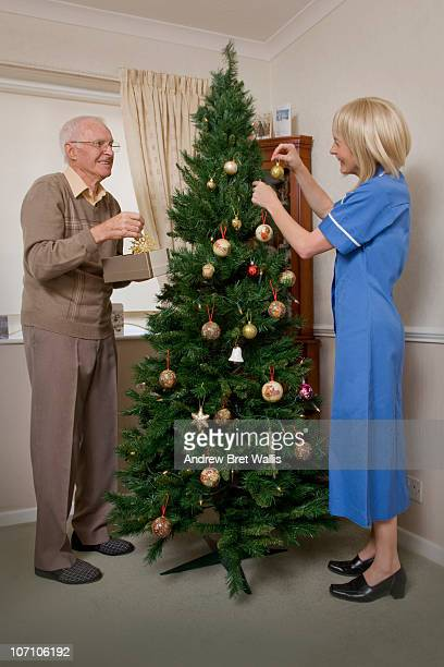 elderly man and carer decorating a christmas tree - christmas decoration stock pictures, royalty-free photos & images