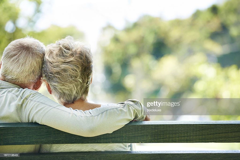 Elderly man and woman embracing on outdoor bench : Stock Photo
