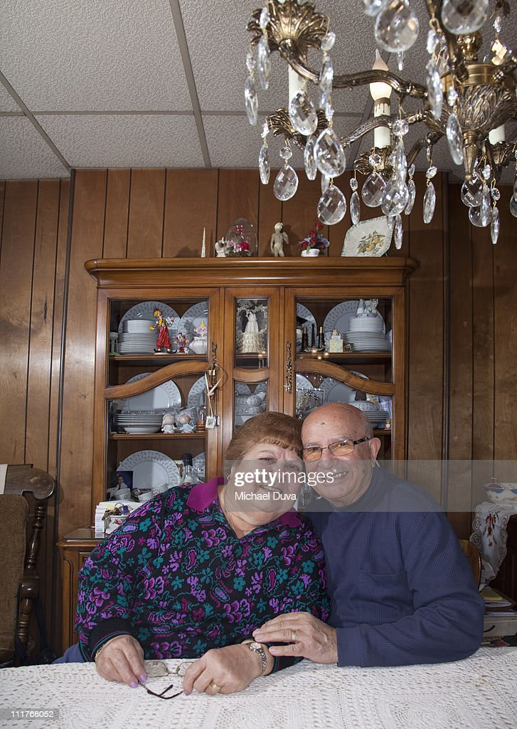 Elderly Man and Woman Sitting at dining table home : Stock Photo