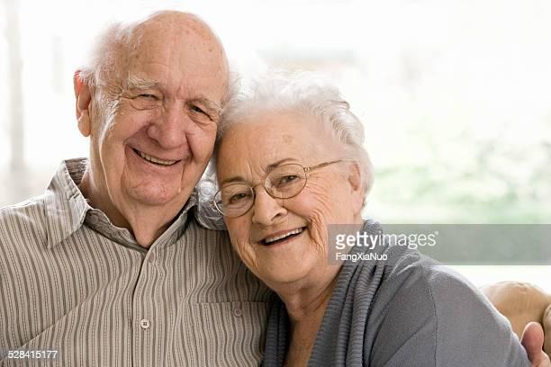 Älterer Mann und Frau sitzen auf Couch