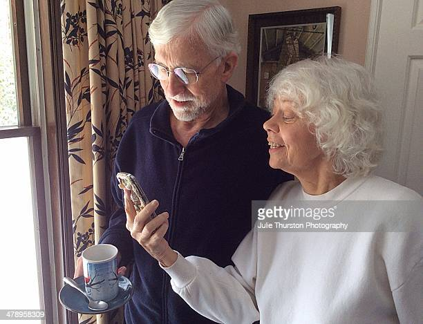 Elderly Man and Woman Smiling and Enjoying Something on Their Phone