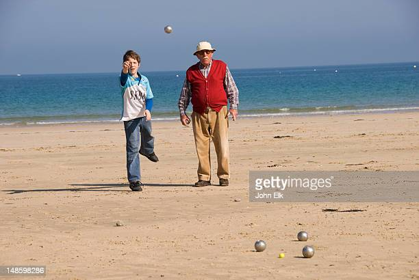 Elderly man and young boy playing petanque on beach.