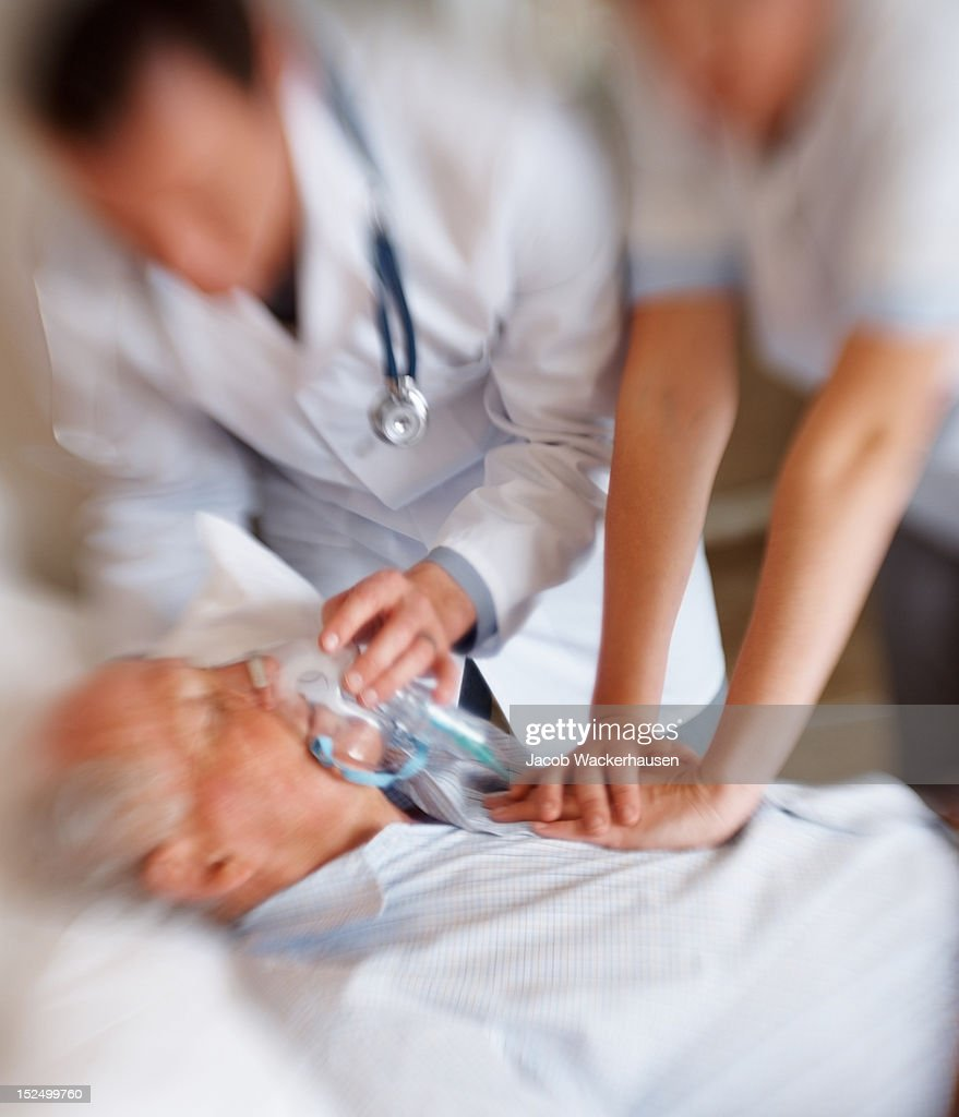 Elderly man being treated for a heart attack : Stock Photo