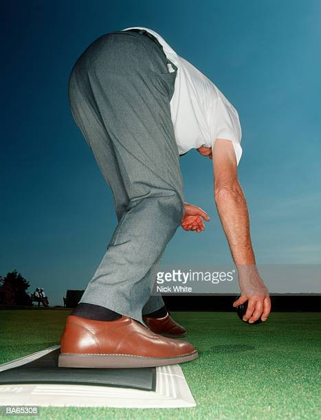 elderly man bending over on bowling green to take shot, close-up - man bending over from behind stock photos and pictures