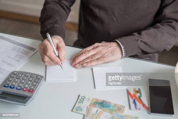 elderly man calculating money for paying bills - bill legislation stock pictures, royalty-free photos & images
