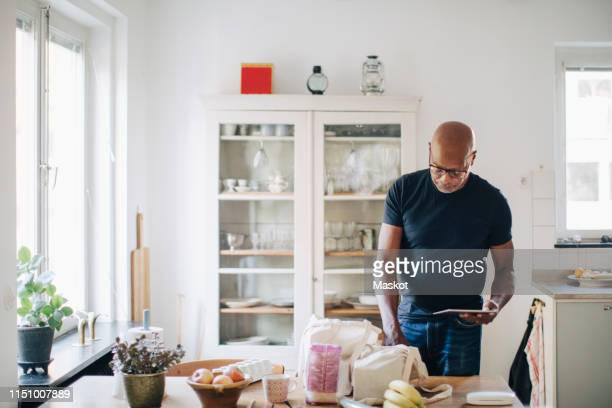 elderly man checking shopping list on digital tablet while removing groceries from bag in kitchen at home - taking off activity stock pictures, royalty-free photos & images