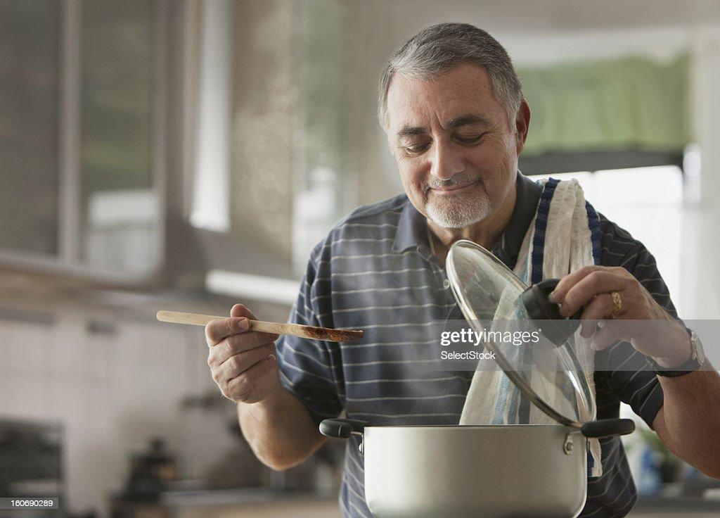 Elderly man cooking : Stock Photo
