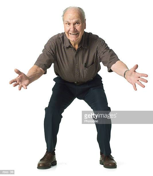Elderly man crouches down with his arms wide open.