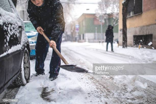 elderly man digging his car out of the snow - city cleaning stock pictures, royalty-free photos & images