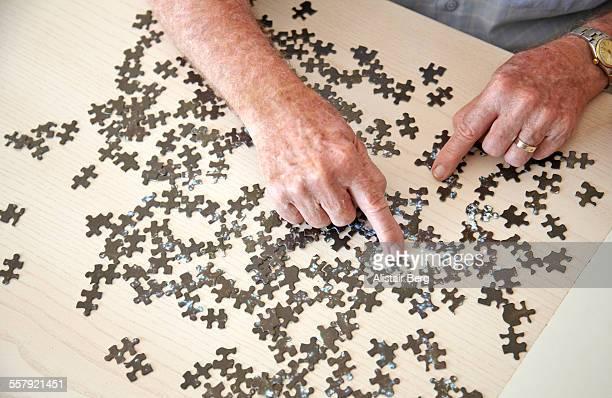 elderly man doing jigsaw puzzle - alleen seniore mannen stockfoto's en -beelden