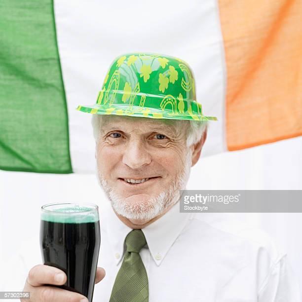 elderly man dressed as a leprechaun holding a glass of stout - einzelner senior stock-fotos und bilder