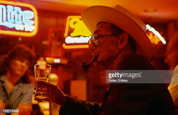 Elderly man drinking beer at bar.