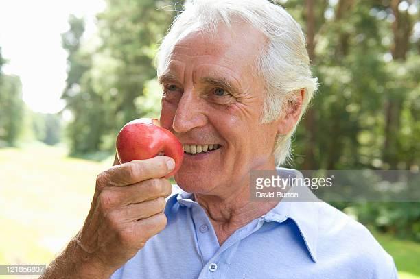 Elderly man eating an apple