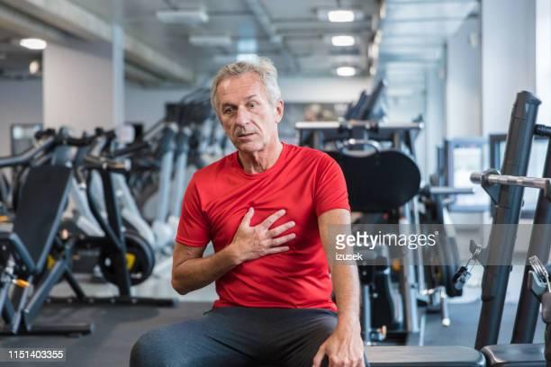 ältere männer, die schmerzen in der brust im fitnessstudio spüren - izusek stock-fotos und bilder