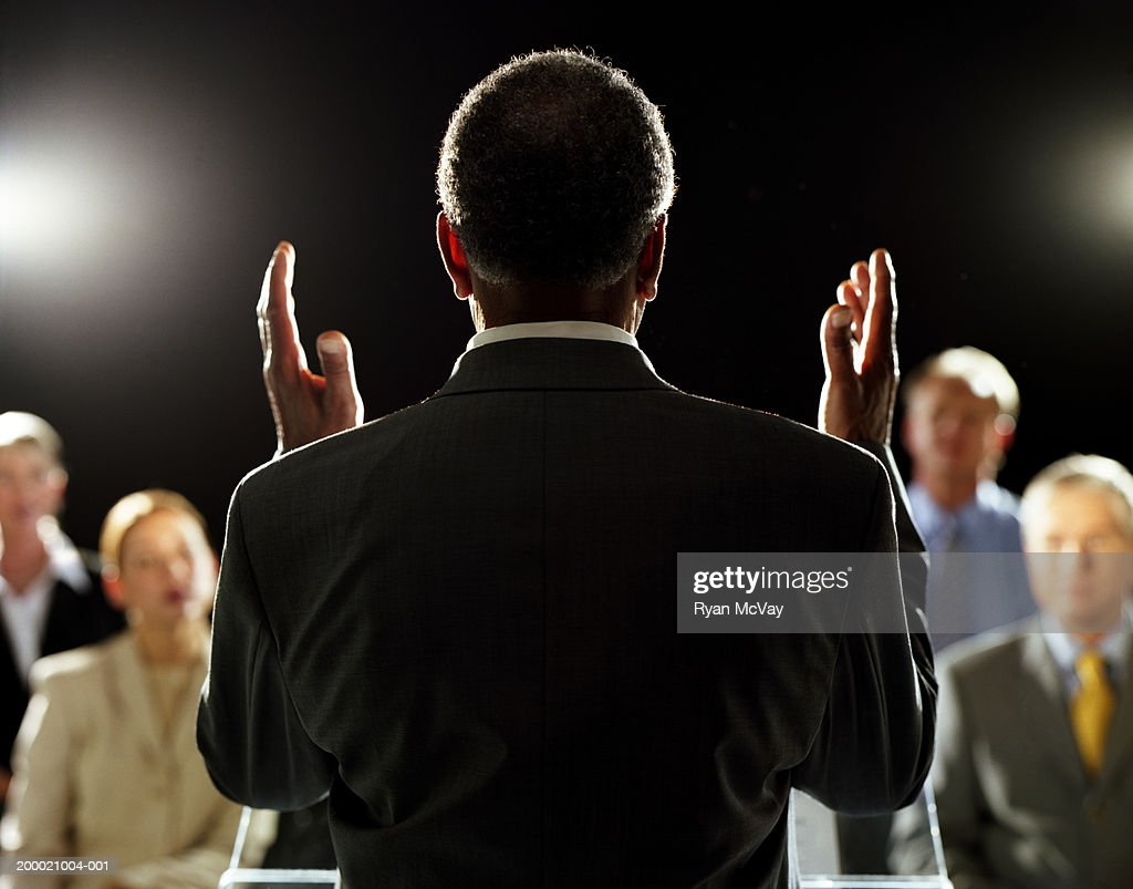 Elderly man giving speech at podium, rear view : Stockfoto