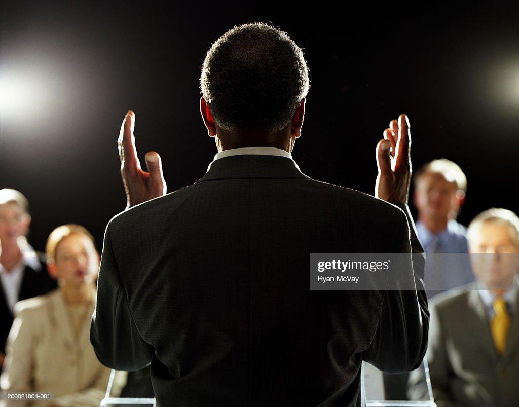 Elderly man giving speech at podium, rear view : Stock Photo