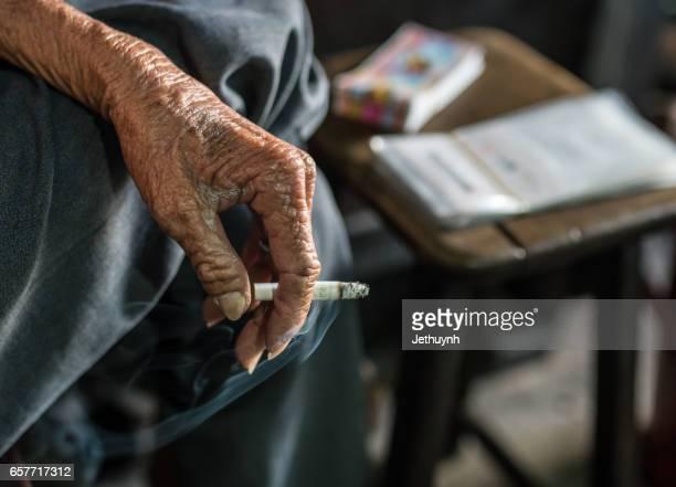 Elderly man hand holding a cigarette