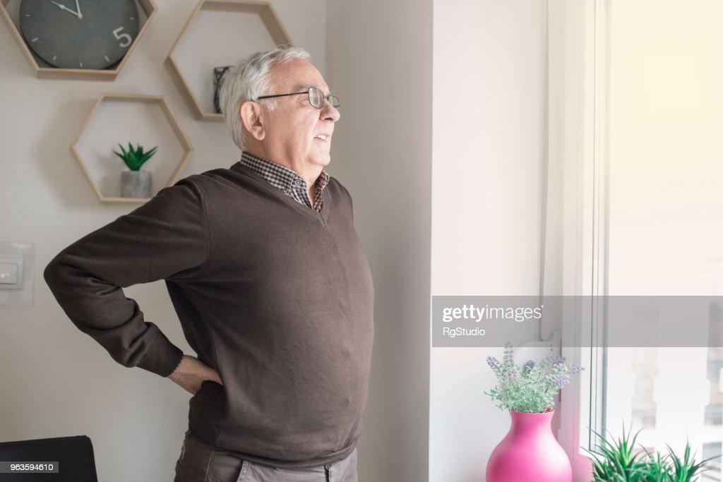 Elderly man having back pain issues : Stock Photo