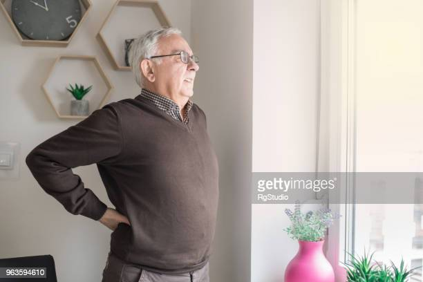 elderly man having back pain issues - torso stock pictures, royalty-free photos & images