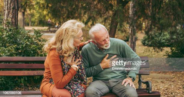 elderly man having chest pains or heart attack in the park - heart attack stock pictures, royalty-free photos & images