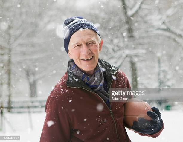 Elderly man holding a football smiling during snow storm