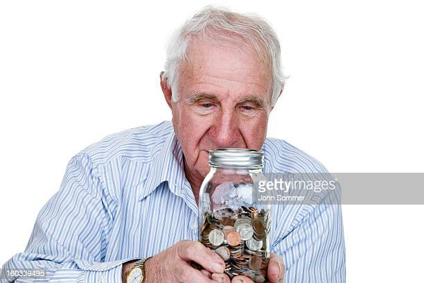 elderly man holding a jar of coins - penny for the guy stock photos and pictures