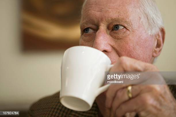 Elderly man holding cup