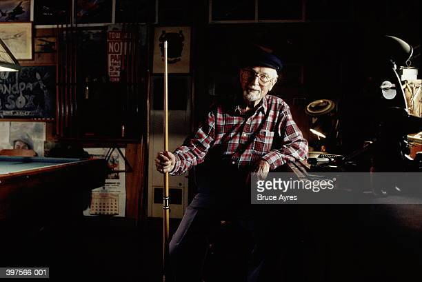 elderly man holding pool cue next to table - old men playing pool stock pictures, royalty-free photos & images