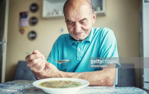 elderly man holds his hand trying to control parkinson disease while eating a soup. - 麻痺 ストックフォトと画像