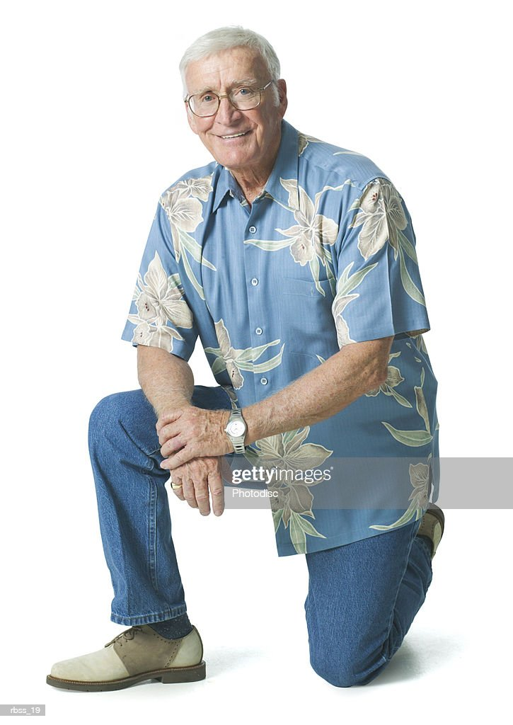 Elderly man in a blue shirt kneels on one knee and grins at the camera. : Foto de stock