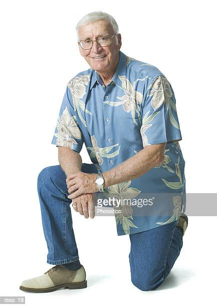 Elderly man in a blue shirt kneels on one knee and grins at the camera.