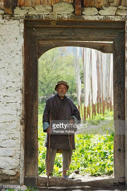 Elderly man in a garden doorway.