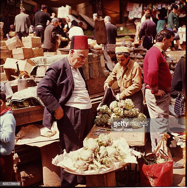 Elderly man in a red fez examines artichokes in a street market in Beirut Lebanon April 1967