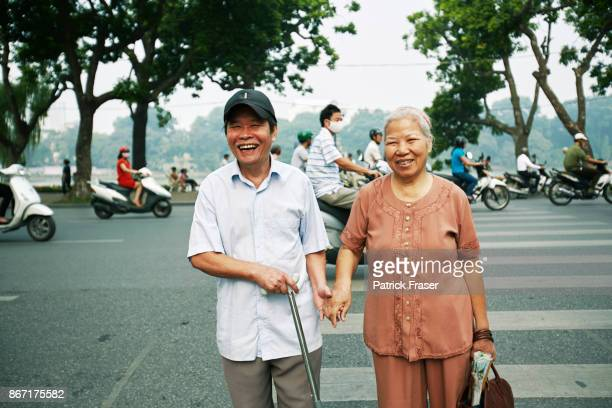 Elderly Man in blue shirt with cane and elderly woman in pink blouse smile and cross busy street