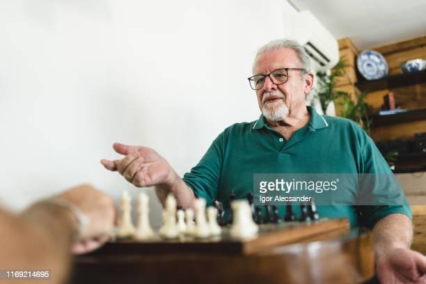 elderly man in doubt playing chess - sentar se imagens e fotografias de stock