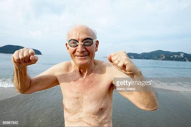 Elderly man in goggles on beach making fist