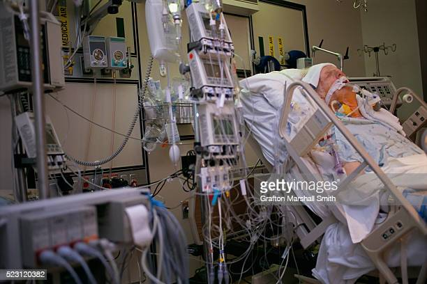 elderly man in intensive care after quad bypass surgery - intensive care unit stock pictures, royalty-free photos & images