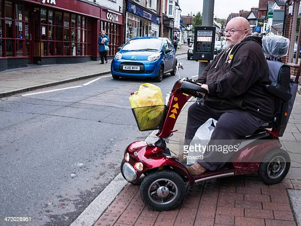 elderly man in mobility vehicle at pedestrian crossing - mobility scooter stock photos and pictures