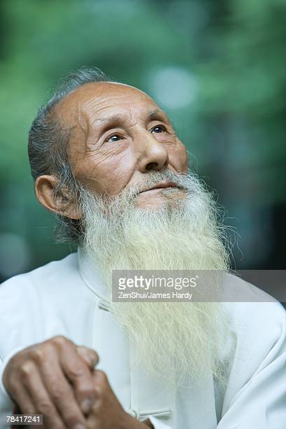 Elderly man in traditional Chinese clothing, looking up, portrait