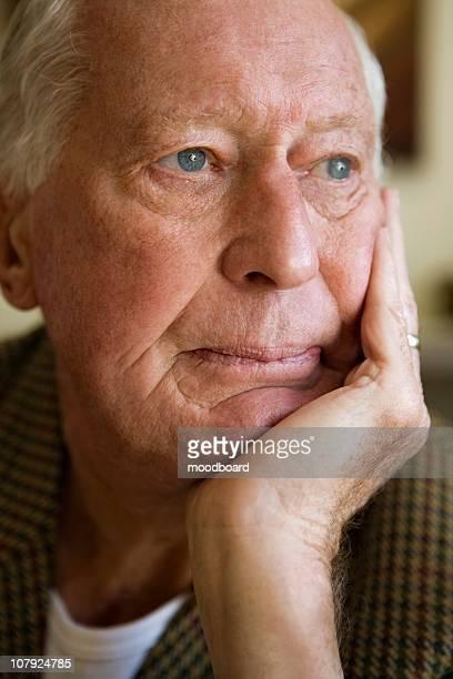 Elderly man leaning head on his hand