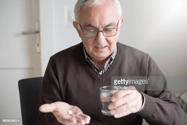 oudere man op zoek naar geneeskunde in zijn hand - medicijnen innemen stockfoto's en -beelden
