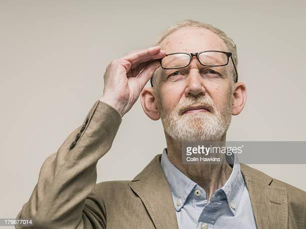 elderly man looking with glasses - curiosity stock-fotos und bilder