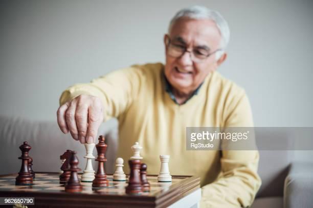 älterer mann macht eine bewegung mit schachfigur - schach stock-fotos und bilder