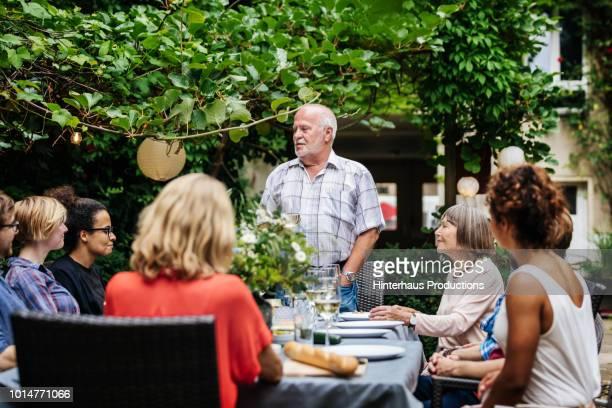 elderly man making speech at family bbq - african american family dinner fotografías e imágenes de stock